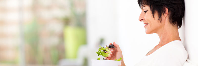 woman smiling, eating a salad