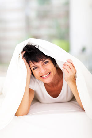 smiling woman looking out from under a blanket