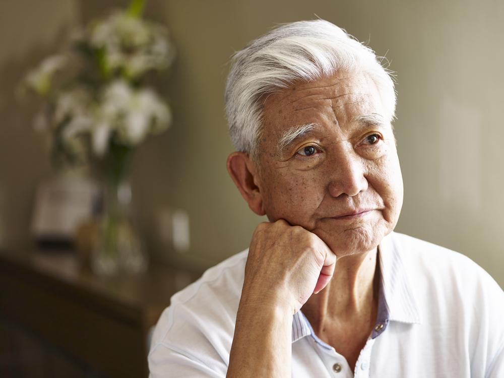elderly gentleman leaning chin on hand